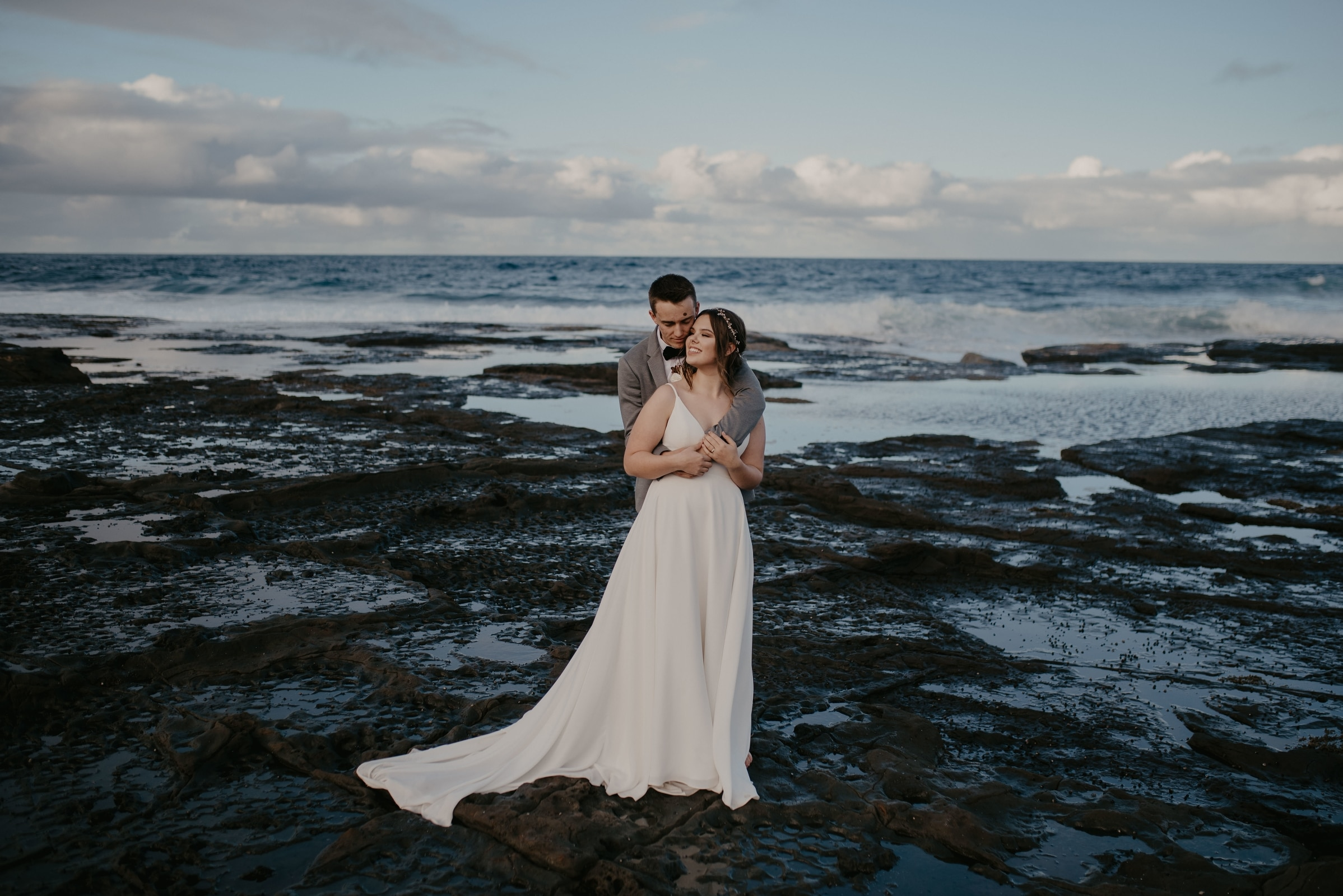 A groom is hugging his bride from behind and kissing her on the cheek. They are standing in the middle of a headland with the ocean making waves behind them. Their adventure elopement photos were taken by Virginia Evan.