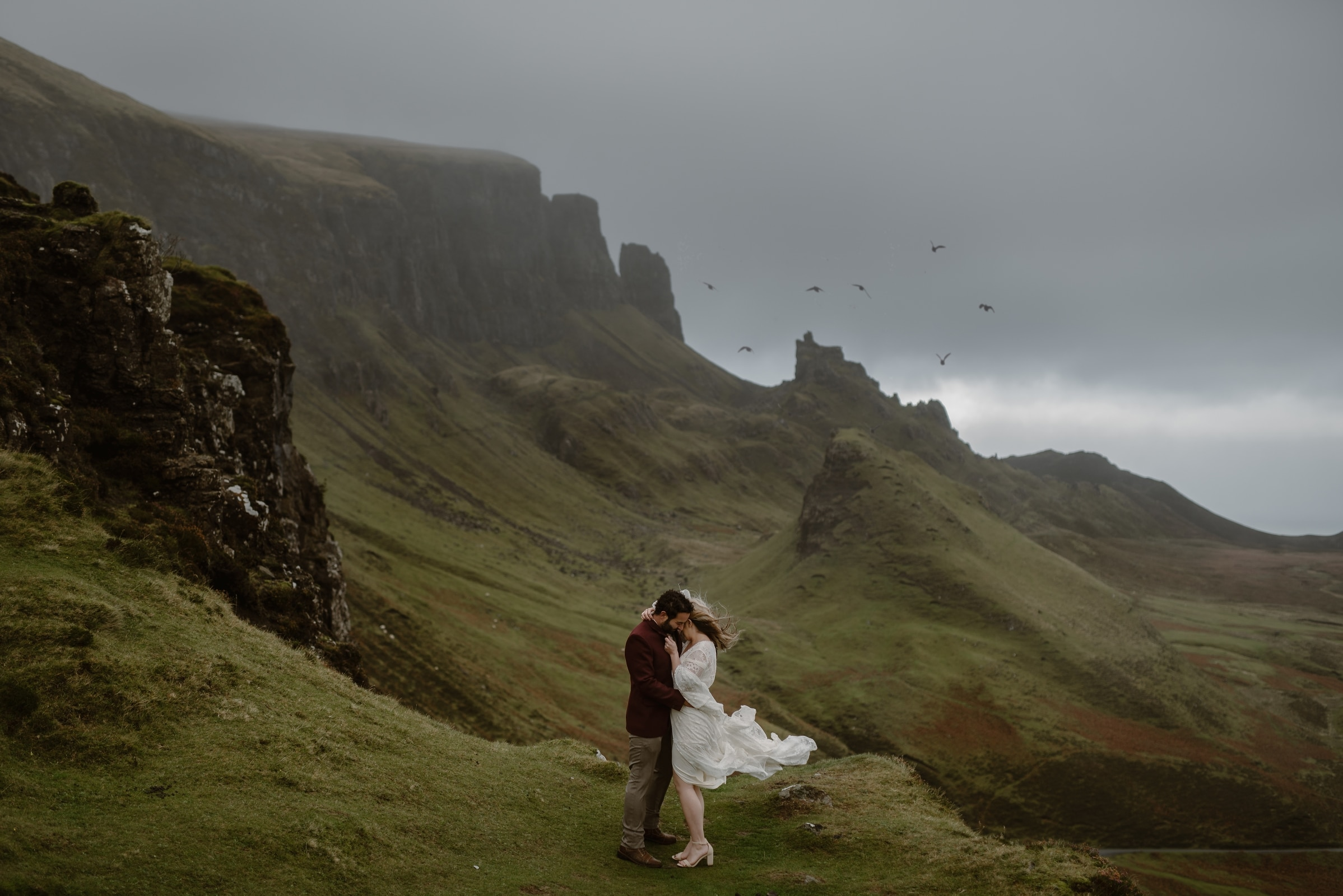 An eloping bride and groom are embracing each other, keeping warm from the intense Scottish winds. Behind them are the jagged mountains of the Isle of Skye. Birds are flying in the distance over the rocks. This is one of the best elopement locations.