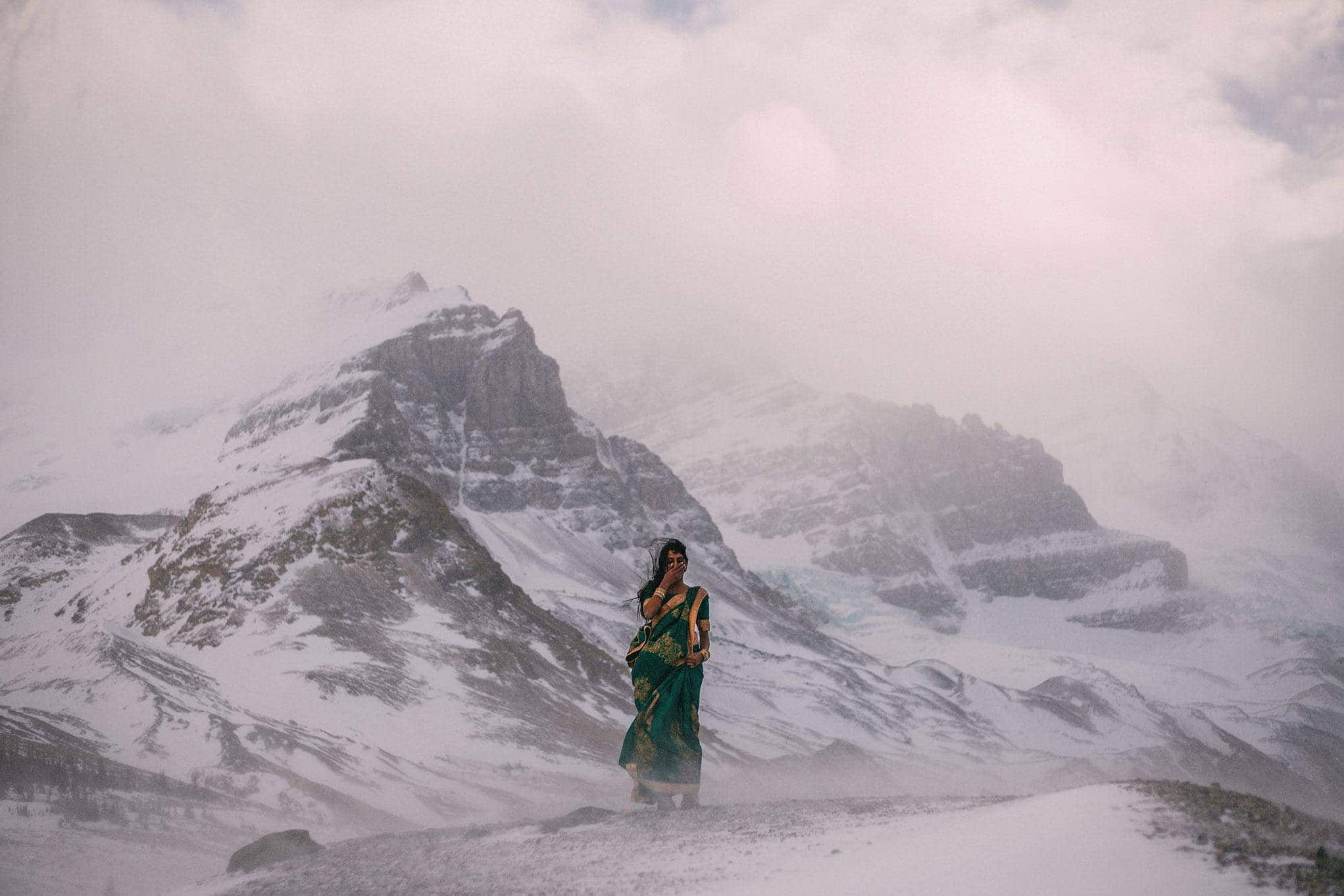 A bride in a sari stands in the middle of a snowstorm covering her mouth while laughing. Behind her are sweeping views of the mountains and a glacier in Banff National Park. This is what an adventurous elopement is made of.
