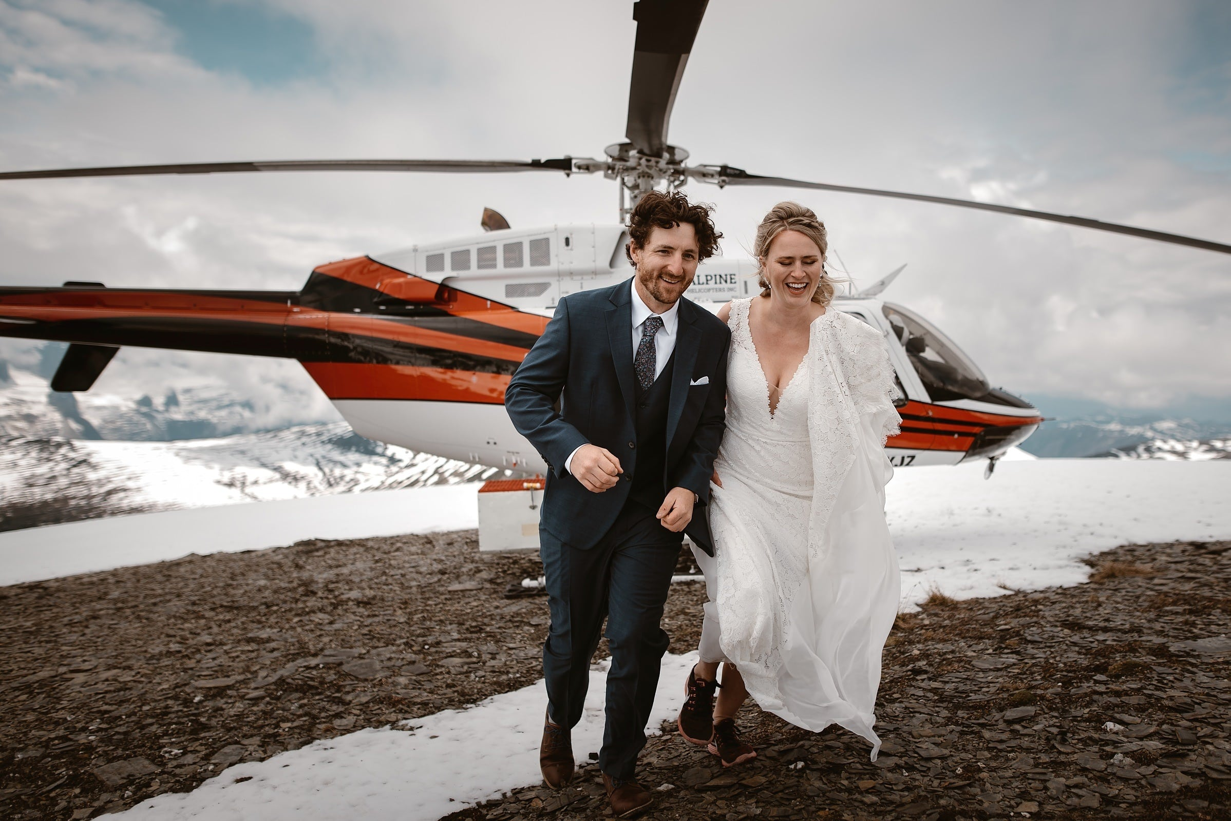 An eloping couple are laughing, and running away from the helicopter that flew them to the top of a mountain in Banff National Park. Their adventurous elopement photos were captured by Virginia and Evan.
