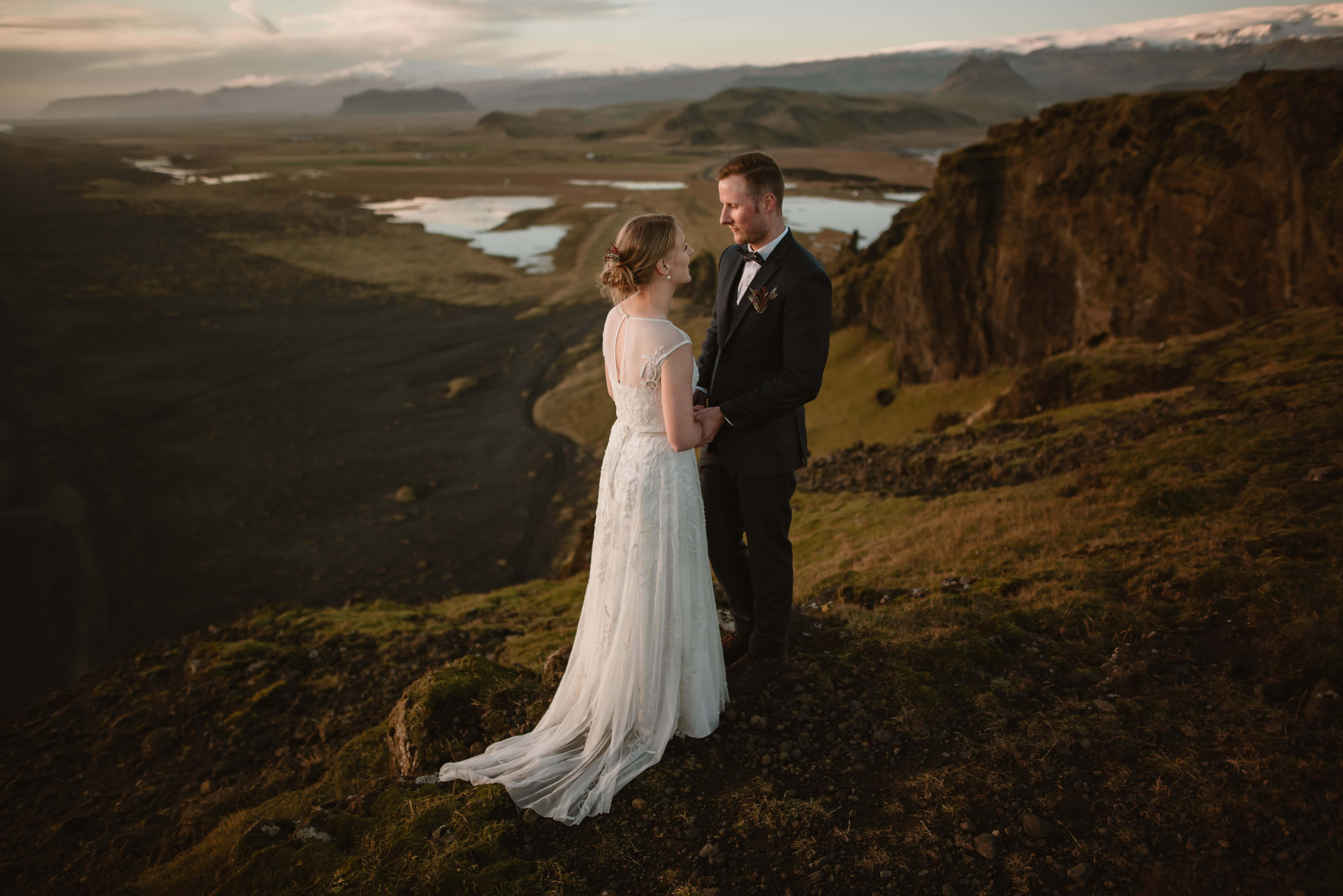 An eloping couple is standing at an incredible viewpoint in Iceland, sharing their vows, face to face, and holding hands. They are overlooking snowy mountains, lakes, and a black beach. When people ask what is eloping, this is the perfect picture.