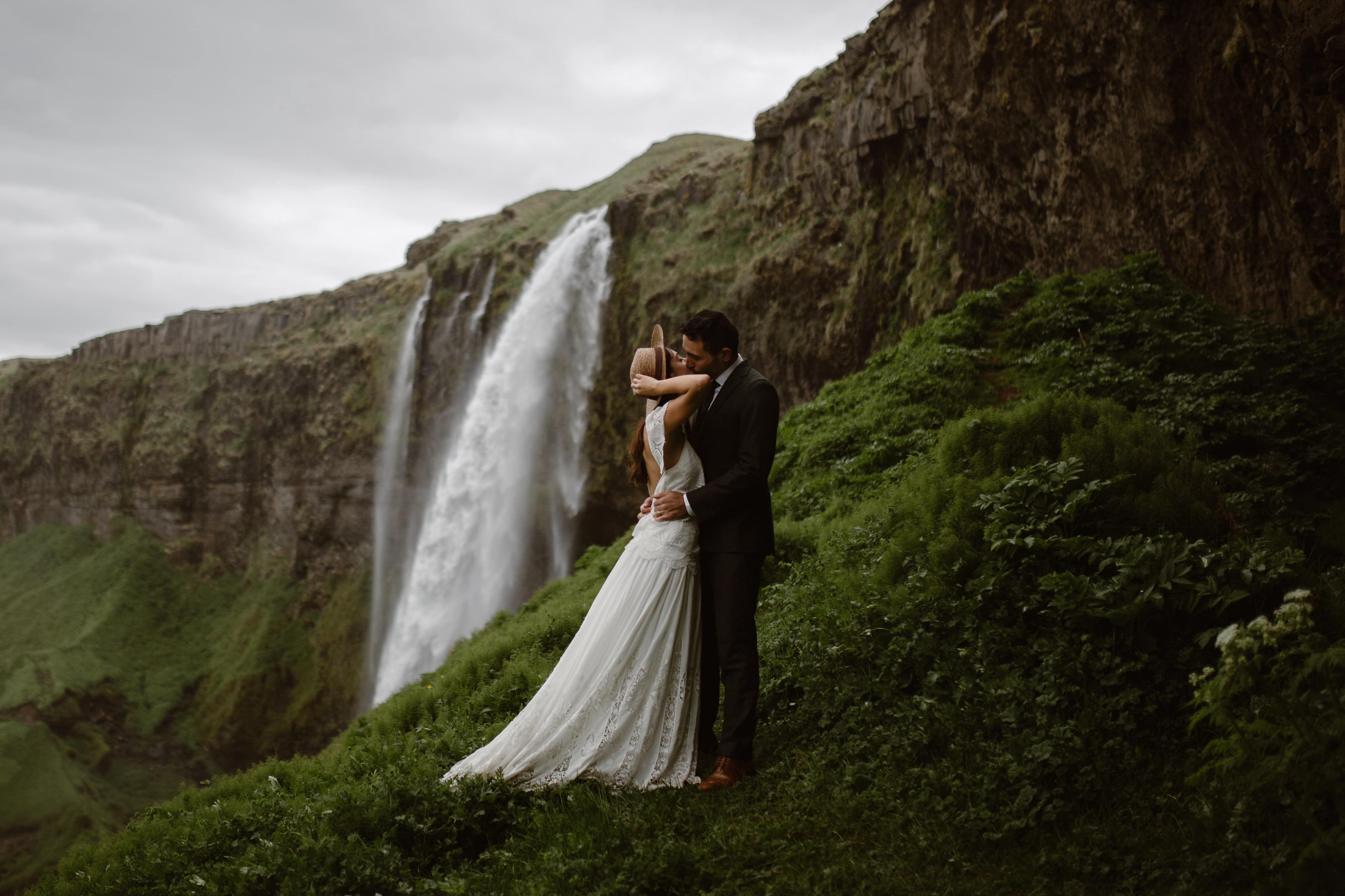 An eloping couple is kissing in front of an epic waterfall in Iceland. The bride is holding onto her wide brimmed hat so it doesn't blow away with the force of the waterfall. When you think of the best locations to elope, Iceland should be on the list.